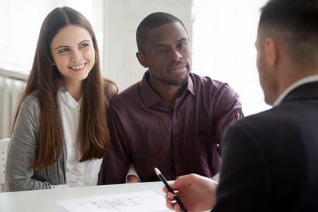 Multiethnic millennial couple visiting real estate agent buying first home together, broker consulting spouses, showing house plan, boyfriend and girlfriend taking mortgage for property purchase.