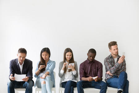 Multiethnic job candidates preparing for job interview, reading cv or resume on electronic devices or papers, diverse applicants waiting for turn in queue for work talk. Hiring, employment, HR concept