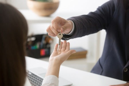 Close up of realtor giving keys to new house to female buyer purchasing first home, broker making deal with potential tenant renting apartment, client buying property from real estate agent.