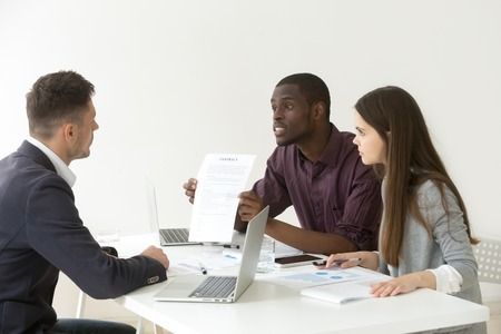 African American worker disagree with Caucasian colleague about contract terms and conditions during company business meeting, partners disputing, black manager blaming coworker for document mistake Stock Photo