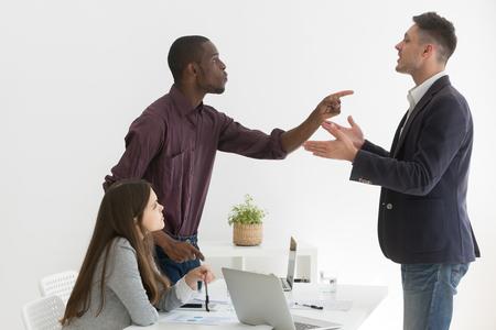 Colegas multiétnicos enojados que discuten durante una reunión de negocios, trabajador afroamericano que culpa al socio caucásico por error, compañeros de trabajo no están de acuerdo con el proyecto, discuten en la sesión informativa de la empresa en la oficina Foto de archivo