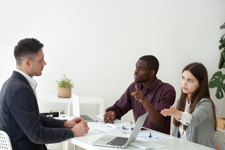 Colegas afroamericanos y caucásicos enojados masculinos que culpan al compañero de trabajo por error grave, disputando y discrepando, mujer apuntando a la puerta pidiendo al socio que salga de la reunión de negocios.