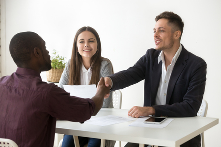 African American work applicant shaking hand of millennial hr agent making good first impression during interview, workers handshaking black candidate greeting newcomer. Recruitment concept Stock Photo - 103952088