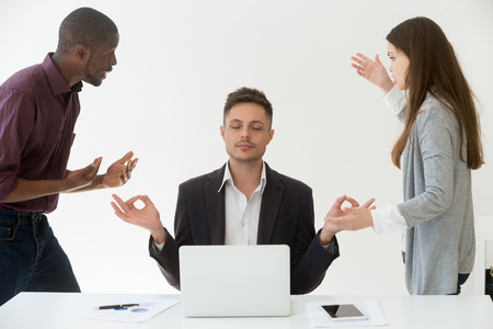 Caucasian male employee meditating, practicing yoga at workplace while multiracial colleagues yelling at him, blaming for business mistake or failure. Stress relief, emotion control, balance concept