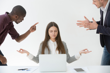 Calm female employee practicing yoga and meditating at workplace, ignoring multiracial colleagues shouting at her, blaming for business failure, woman relieving work stress. Emotion control concept 스톡 콘텐츠