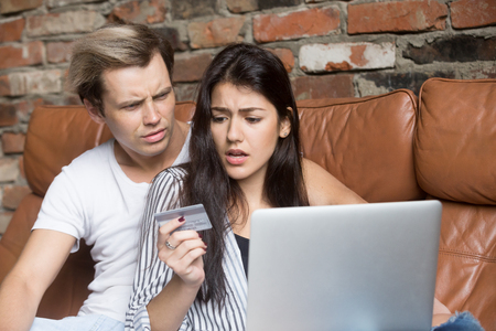 Frustrated couple sit on sofa shopping online shocked having credit card problems, woman and man disappointed getting notification about insufficient funds on bank account, having financial troubles