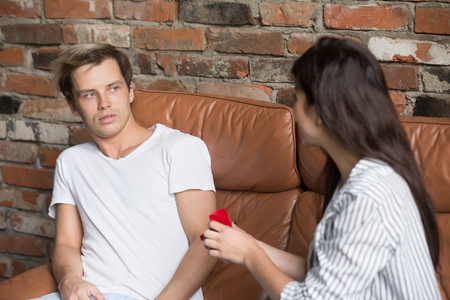 Young decisive girlfriend takes initiative in her hands, making marriage proposal to surprised boyfriend, woman proposing to puzzled man doubting about future actions. Concept of feminism, engagement Stock Photo