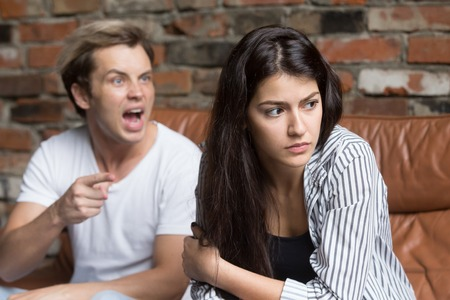 Young millennial upset couple arguing, having family misunderstanding or fight, angry husband yelling at wife, blaming her for relationship problems, sad offended woman ignoring husband avoiding talk