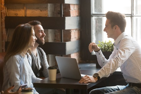 Male architect talking to smiling millennial couple, consulting on housing project, realtor explaining mortgage and contract condition to excited young couple during friendly meeting in coffee shop Reklamní fotografie - 104216209