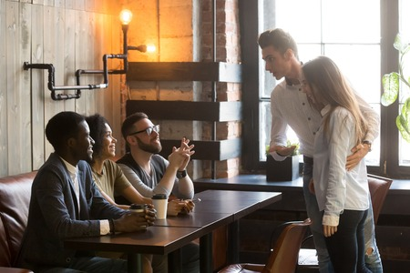 Caucasian man introducing girlfriend to multiracial millennial friends sitting at table, enjoying coffee in cafe, male worker acquainting colleagues with new female employee at meeting in coffeeshop
