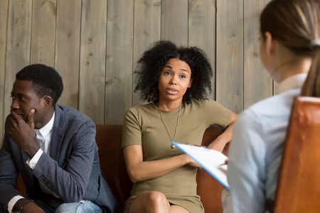 Black millennial couple visiting therapist office, upset African American wife discussing marriage problems and complaints with psychologist during session with husband. Family counsel concept