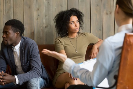 African American spouses avoiding to talk after family fight, wife and husband visiting psychologist undergoing marriage therapy session, couple breaking up, seeking help from relationship counsellor Stock Photo