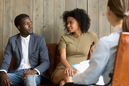 Reconciled black husband and wife looking at each other after successful psychological treatment from relationship counselor, African spouses make peace at therapy session, lovers ready to compromise Stock Photo