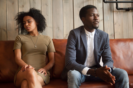 Mad African American husband and wife ignoring each other, not talking, millennial couple in fight sitting apart on couch not ready to compromise, stubborn spouses cannot make peace, break up concept Reklamní fotografie