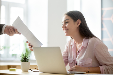 Satisfied female company intern happy to see good work results, receiving document report from employer, student get high evaluated sheet, excited to see professional growth and success