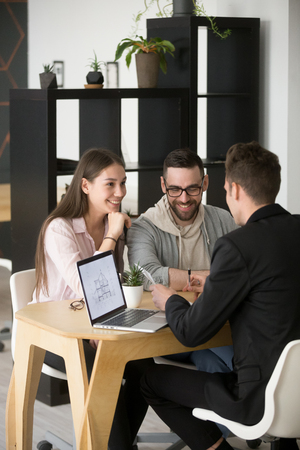 Architect or designer discussing house plan with excited millennial buyers couple visiting his office, broker or realtor show apartment project to husband and wife buying or taking mortgage together
