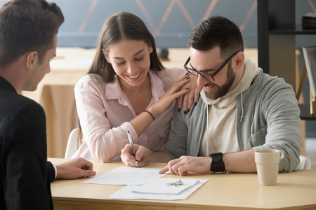 Excited millennial couple signing purchase agreement buying first home together, husband puts signature on document, becoming apartment owner, spouses legalize property ownership in realtor office