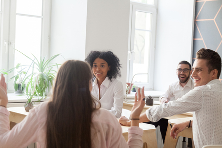 Excited employees sharing female worker success or achievement, multiracial colleagues surprised with great achievement of their coworker, group of freelancers or students shocked by lottery win