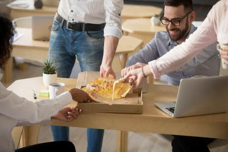 Happy diverse colleagues take pizza slices, spending lunch break in office together, coworkers celebrating enjoying ordered takeout service with meal, workers eating dinner at workplace. Close up Stock Photo