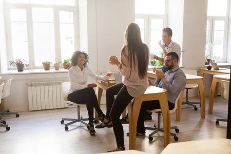 Trabajadores multirraciales felices que se divierten disfrutando de la pizza juntos, empleados que pasan el almuerzo en la oficina hablando y riendo, diversos colegas sonrientes que han pedido comida para llevar en la oficina charlando Foto de archivo