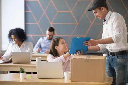 Young deliveryman giving female employee documents to sign after delivering parcel in card box, male courier asking woman put signature on paper handing over ordered package in office.