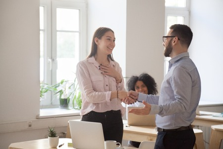 Male boss congratulating female employee handshaking and greeting her on special occasion, happy employer shaking hand of woman worker complimenting with promotion of good work results. Reward concept Stock Photo