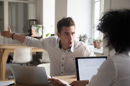 Mad male worker yelling at female colleague asking her to leave office, multiracial coworkers disputing during business negotiations, employees cannot reach agreement, blaming for mistake or crisis Imagens