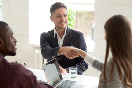 Smiling male worker shaking hand of young female colleague at business meeting, multiracial coworkers cooperating, partners handshaking greeting or making good first impression at briefing in office