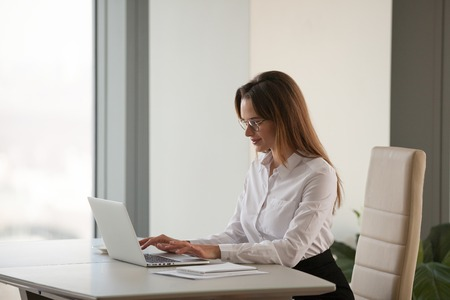 Successful businesswoman working at laptop in modern office in business center, confident female ceo busy at computer, closing deals online, consulting clients, boss woman browsing internet Stock Photo