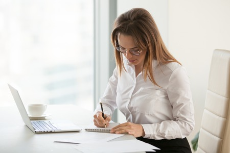 Thoughtful businesswoman taking notes working at laptop in business office, serious female boss writing down information in notebook, focused woman checking financial reports, drinking coffee at work Stockfoto