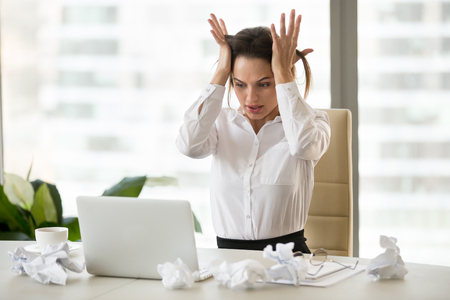 Stressed businesswoman feel despair sitting at desk with crumpled papers, unable to finish work or financial report till deadline, frustrated female employer panic seeing unexpected laptop malfunction
