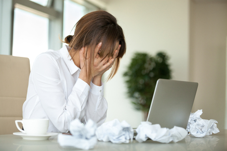Stressed female worker feel despair surrounded by crumpled paper not able to write business letter or email, tired upset businesswoman have no motivation at work, suffering from headache or fatigue Imagens