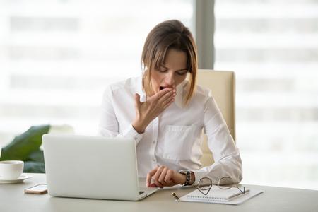Trabajadora agotada bostezando mirando el reloj, esperando que termine la jornada laboral, empresaria aburrida y cansada comprobando el tiempo para salir de la oficina, empleada perezosa contando minutos para terminar o terminar el turno