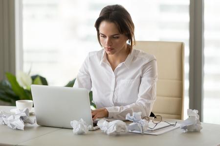 Unmotivierte Geschäftsfrau, die mit zerknittertem Papier am Schreibtisch sitzt und versucht, am Laptop zu arbeiten, verärgerte Mitarbeiterin hat keine Inspiration, versucht, den Bericht zu beenden oder einen Geschäftsbrief zu schreiben