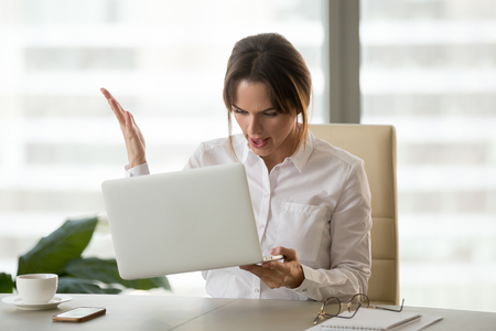 Angry businesswoman holding laptop, mad about gadget malfunction, furious employer feel nervous about error message or notification at computer screen, woman have software problem or failure