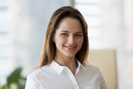 Portrait of smiling businesswoman looking at camera during professional company photoshoot in office, headshot of successful confident female employee posing for picture, happy millennial woman photo