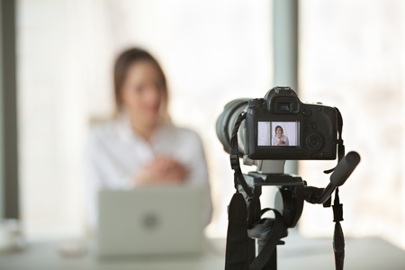 Professional video camera recording successful businesswoman giving online training or filming business course, digital device shooting vlog or interview of company boss or streaming live presentation 写真素材