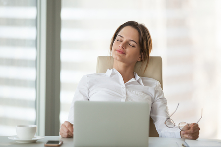 Relaxed businesswoman leaning in chair with eyes closed, resting and meditating in office, calm female ceo taking off glasses, relieving work stress, dreaming of future success and achievements. Archivio Fotografico