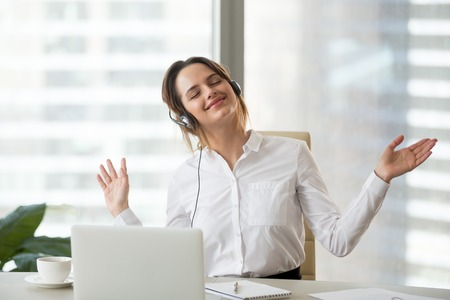 Happy female employee wearing headset listening to favorite music or tracks at laptop, smiling businesswoman relaxing in office chair, dancing to rhythm during work break, enjoying radio hits Stock Photo