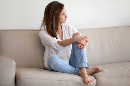 Sad millennial woman sit on couch looking far away, thinking about problems with boyfriend, upset female feel lonely, having depression, contemplated girl disappointed to spent weekend at home alone Stock Photo