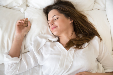 Top close up view of relaxed young female sleeping well on oft white pillows under warm fluffy duvet, calm woman resting in bedroom, being asleep seeing sweet dreams, girl taking nap in cozy bed Banco de Imagens