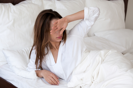 Frustrated young woman wake up in morning feeling bad, having bad sleep, sleepy millennial female have hangover and strong headache after sleepless night, girl suffer from bright light or sunny rays Imagens - 105719868