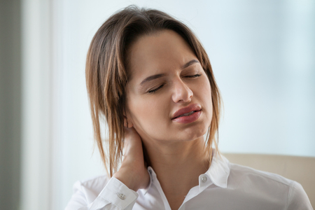 Close up of exhausted millennial female worker massage neck, suffering from muscle pain working long hours in incorrect posture, tired businesswoman relieve discomfort from sedentary lifestyle 스톡 콘텐츠 - 105870219