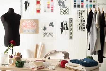 Kreativer Modedesigner Schreibtisch oder Arbeitsplatz mit Nähausrüstung, Stoffen, Vorlagen, Inspirationsbüro für moderne Stylisten, Schneideratelier mit Schaufensterpuppe und Kleidung auf Kleiderbügeln, Couturier-Showroom Standard-Bild
