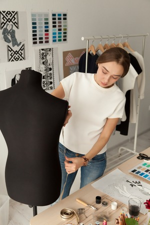 Female fashion designer measuring mannequin creating clothes line in ethnic studio, dressmaker girth dummy with tape preparing unique capsule collection in exclusive design showroom or workshop