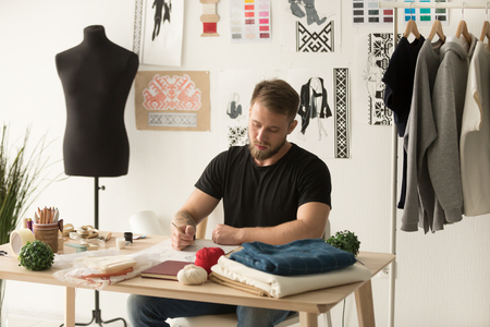 Serious male fashion designer drawing sketch of new clothes collection in ethnic design studio, man tailor creating line, working with brush or pencil on personal desk, developing embroidery pattern Фото со стока