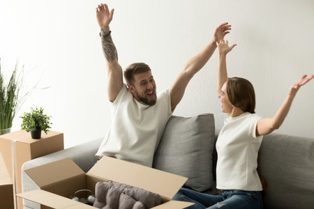 Happy candid husband and wife raising hands up, screaming excited to move in first home, millennial apartment owners celebrating relocation to shared flat purchased, young couple start living together
