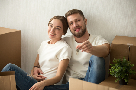 Portrait of excited husband and wife sitting on floor of first house, happy couple holding keys to new home glad to move in shared apartment, young spouses hugging enjoying relocating to own property