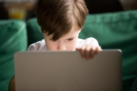 Curious interested kid boy secretly looking watching forbidden censored adult only internet online video content on laptop alone, parental protection, computer control and security for child concept Foto de archivo