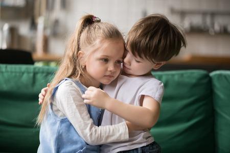 Kleine jongen knuffelen troostende boos meisje zittend op de Bank, jongen broer omhelst triest zus verontschuldigend of geruststellend, broers en zussen vriendschap, kleuters goede relaties en ondersteuning concept